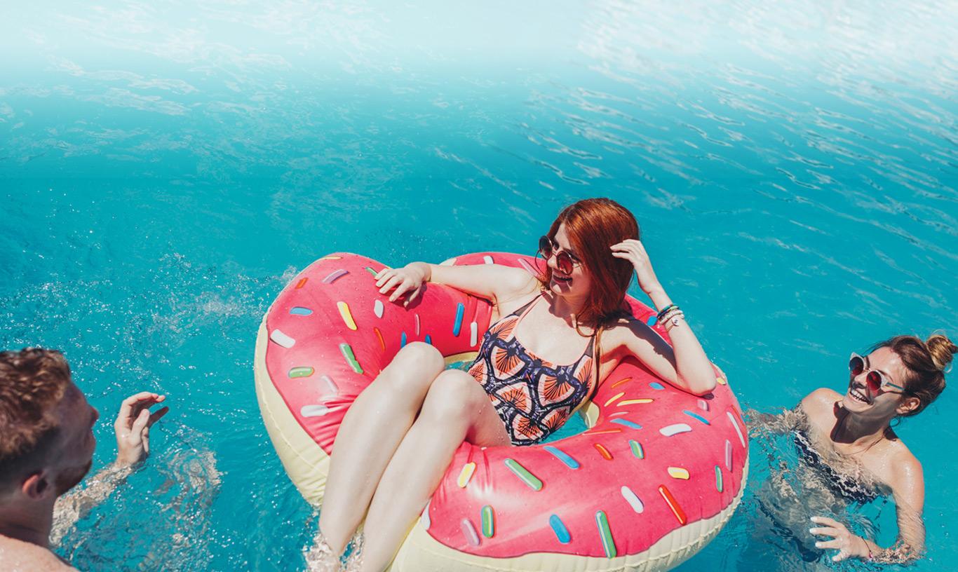 A girl sits on a doughnut floaty.