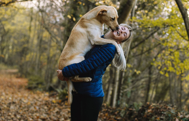 woman with dog in woods laughing and hugging