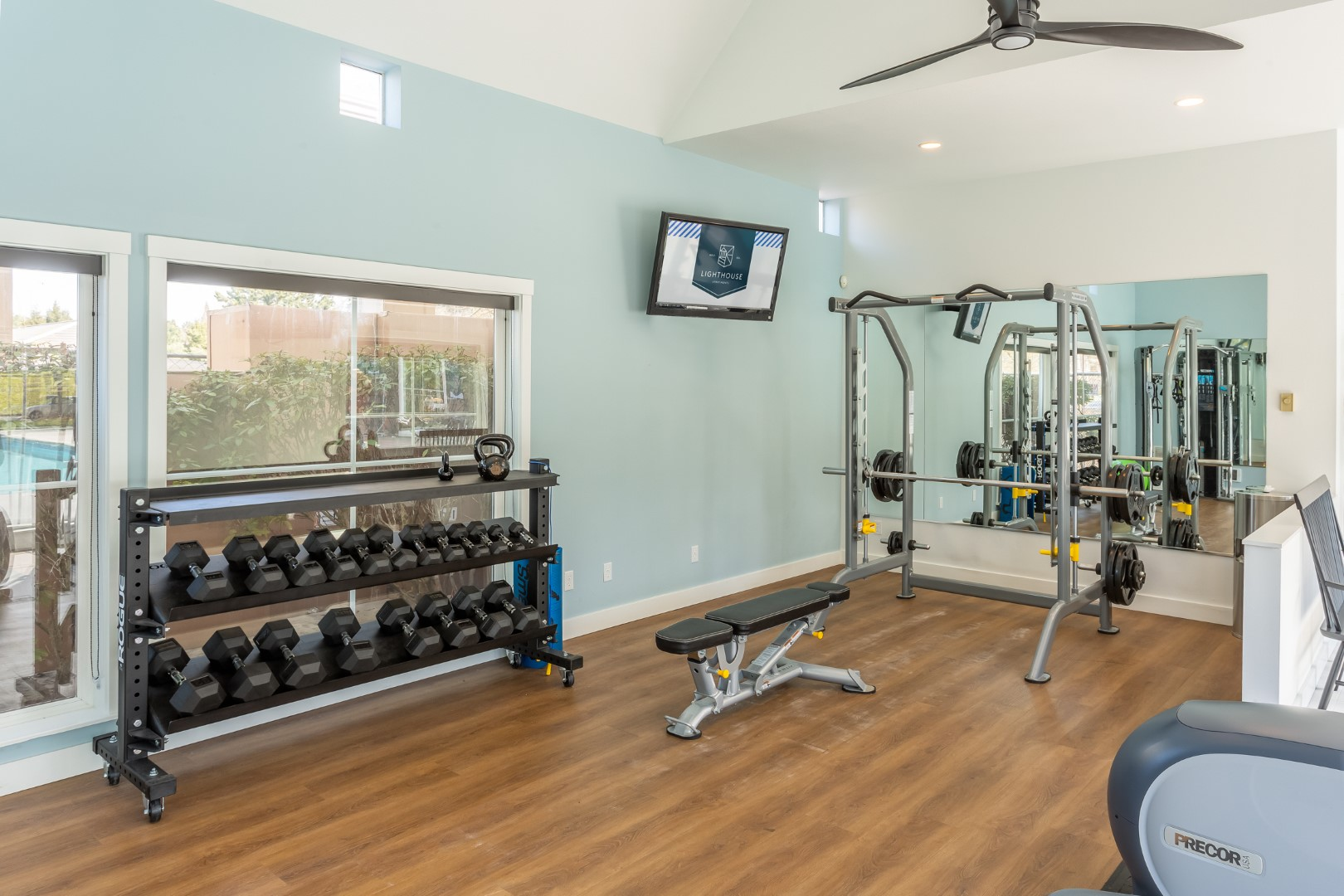 A weight rack sits against the wall in this weight room.