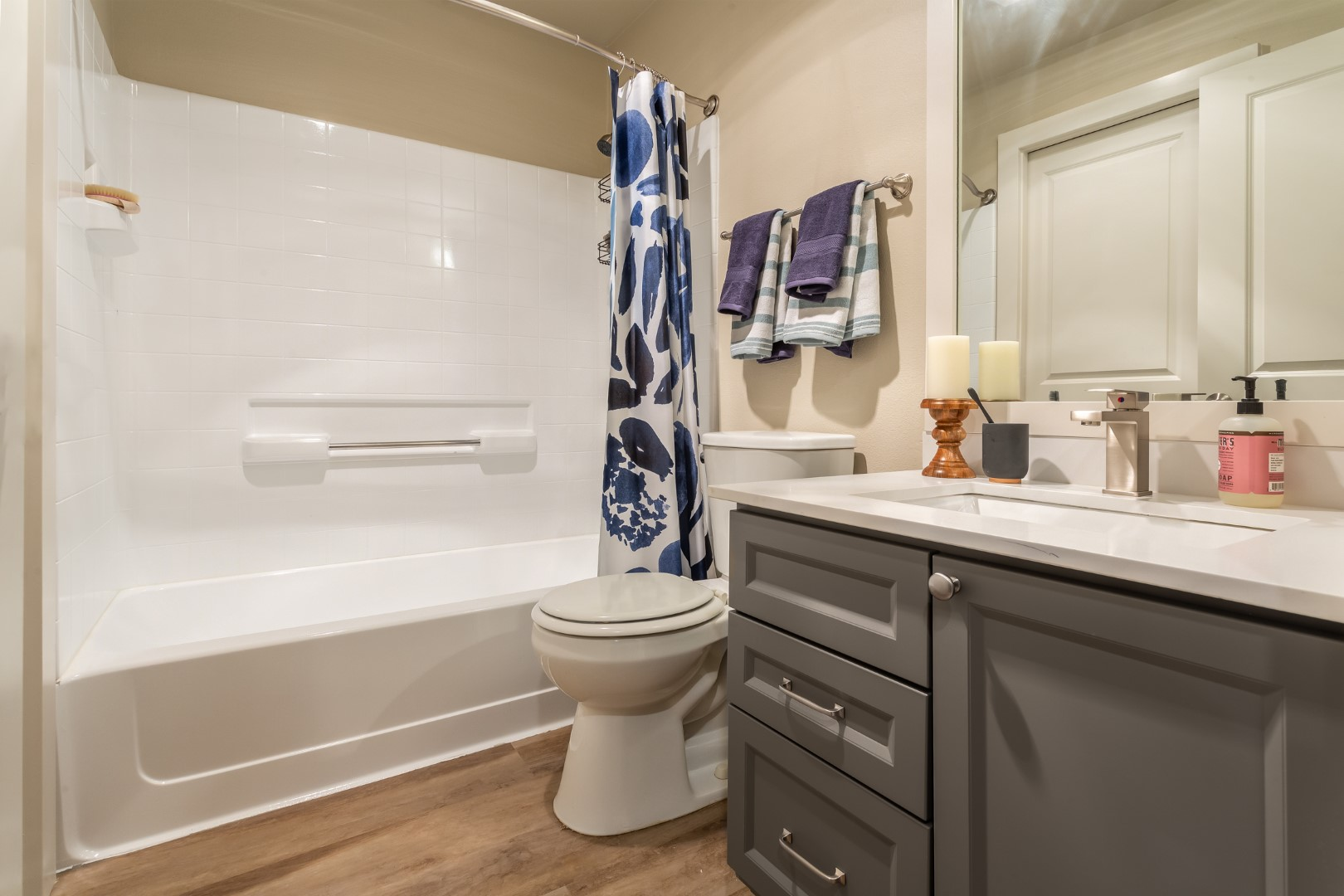 The shower curtain is pulled back to show the tub and shower surround.