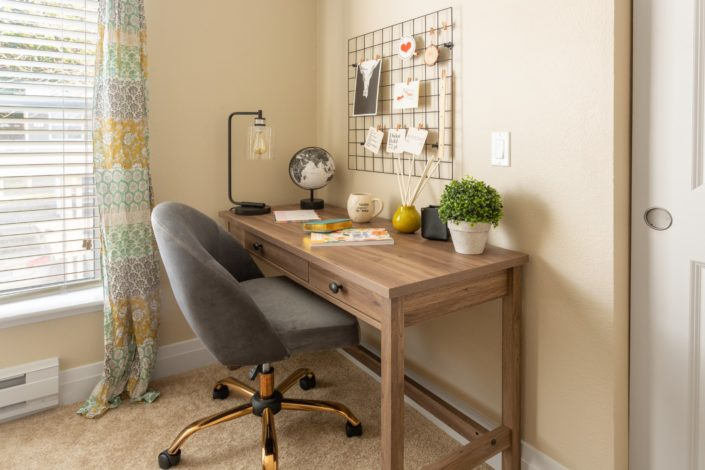 A cute work desk with a fabric rolling chair.